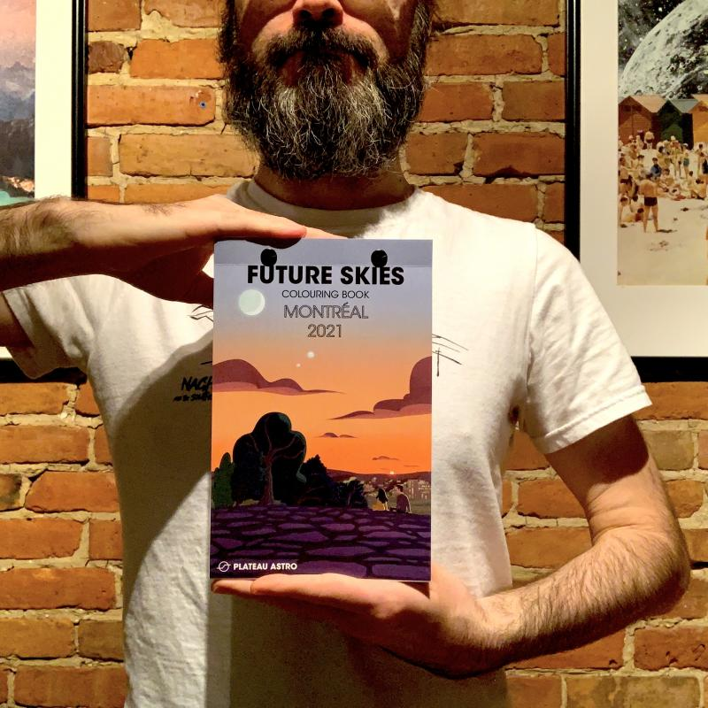 "Trevor holding a 5.5"" by 8.5"" Future Skies Colouring Book"